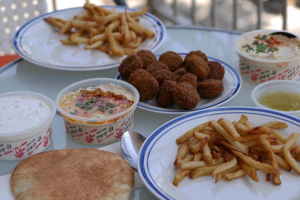 Günstige Speisen vom Abu Hasan. Ein Tisch mit Hummus, Masabacha, Labaneh, Falafel, Pommes und Pita