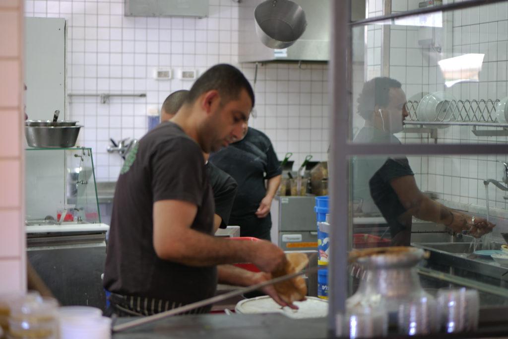Abu Hasan Küche. Vier Person mit schwarzen T-Shirts kochen. Tel Aviv.