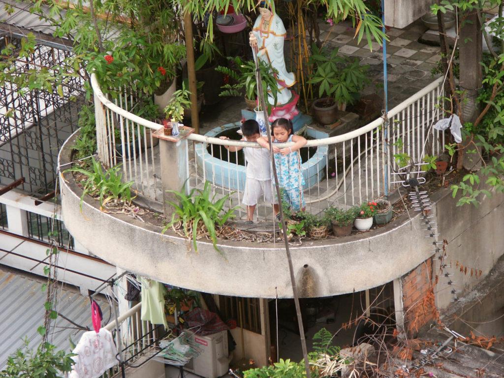 Zwei Kinder auf einem Balkon mit vielen Pflanzen in Saigon