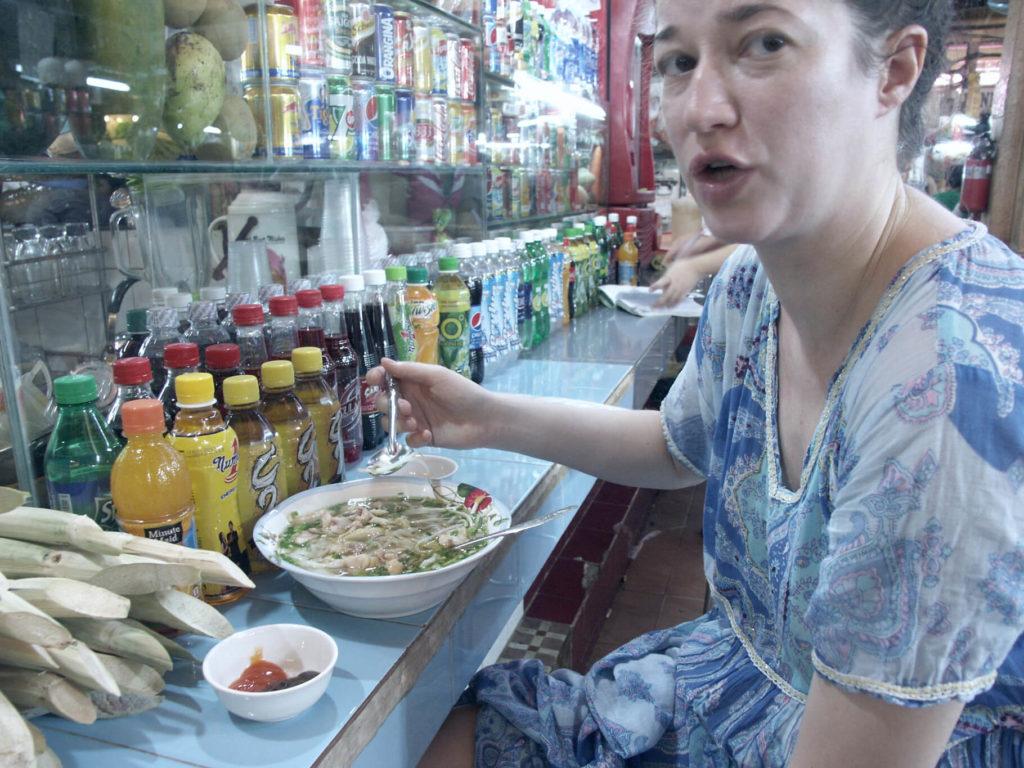 Eine Frau im blauen Kleid isst eine scharfe Nudelsuppe im Ben Thanh Markt Saigon