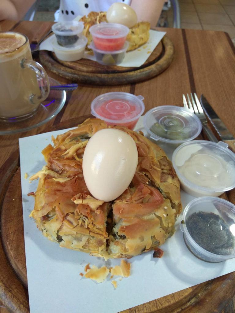 Frühstück bei Leon Bakery. Blätterteig mit Spinat, Ei, Saucen und Milchkaffee. Tel Aviv.