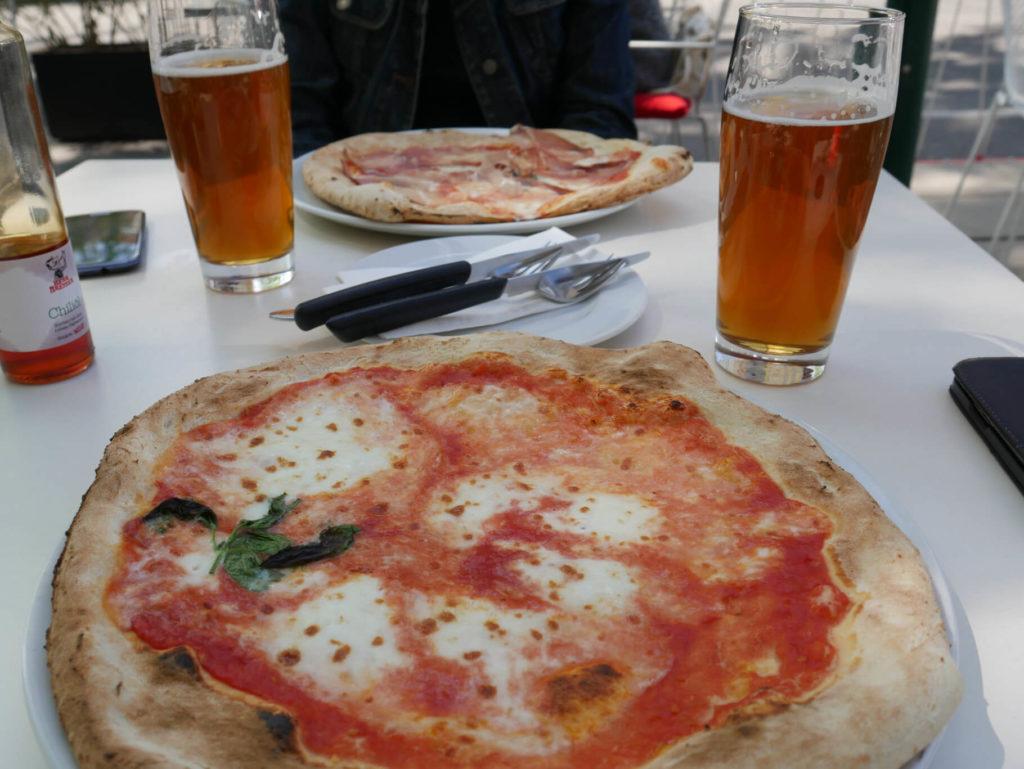 Zwei Pizzen und zwei Bier am Tisch