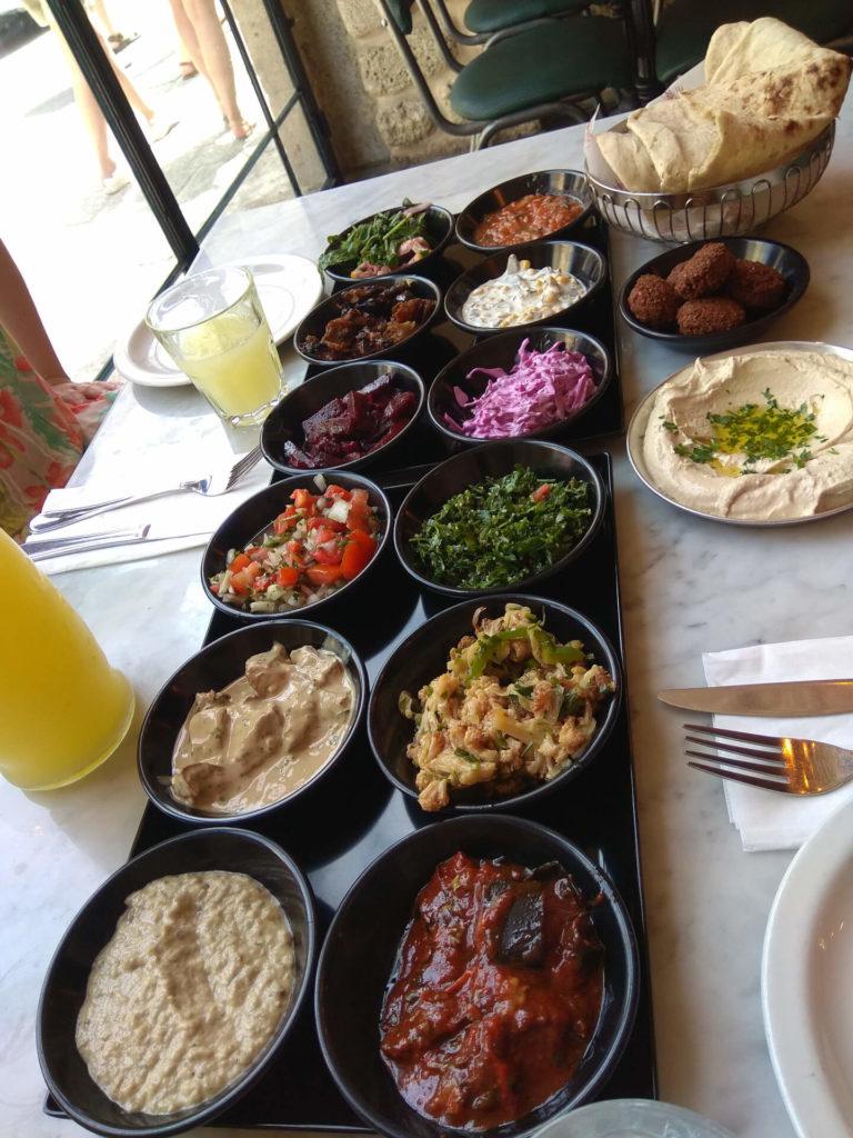 Ein voller Tisch mit Vorspeisentellern bei Shawarma Abulafia in Jaffa