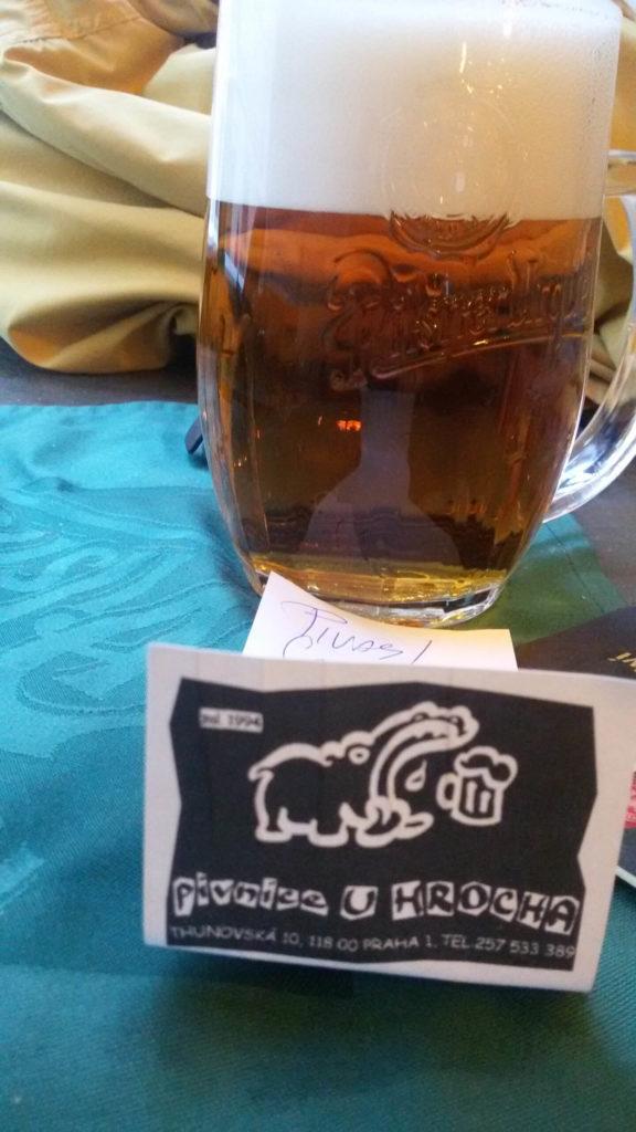 Volles Pilsner Urquell Glas mit Nilpferd Karte im Vordergrund. Prag