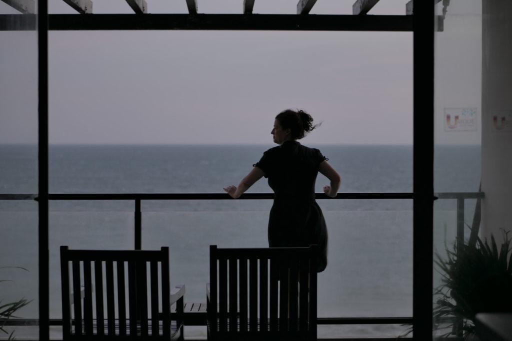 Unique Mui Ne Hotel. Eine Frau steht auf dem Balkon und sieht sich das Meer an. Vietnam.