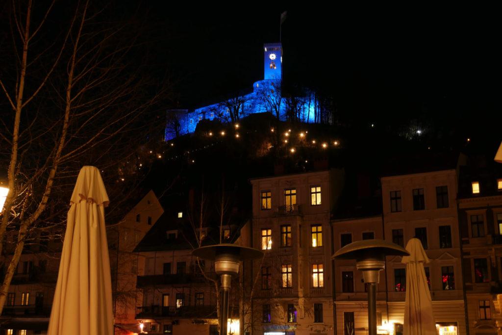 Blau beleuchtete Burg bei Nacht in Ljubljana